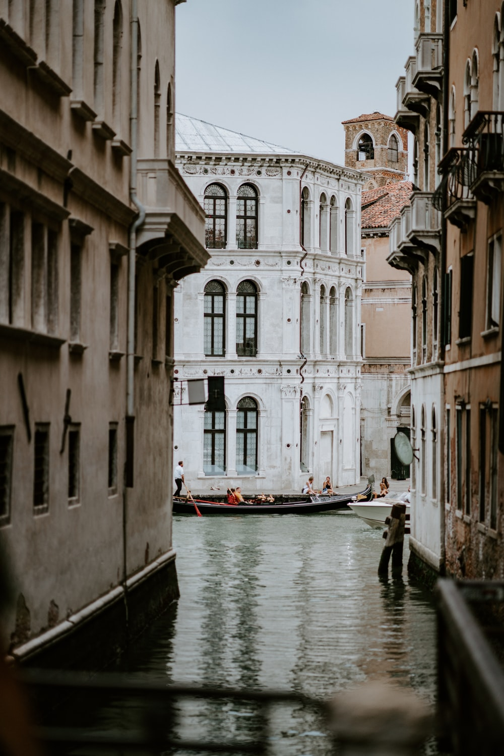 canal between beige and white concrete buildings at daytime