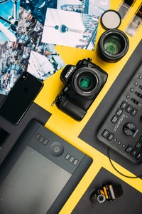 black Nikon DSLR camera beside space gray iPhone X