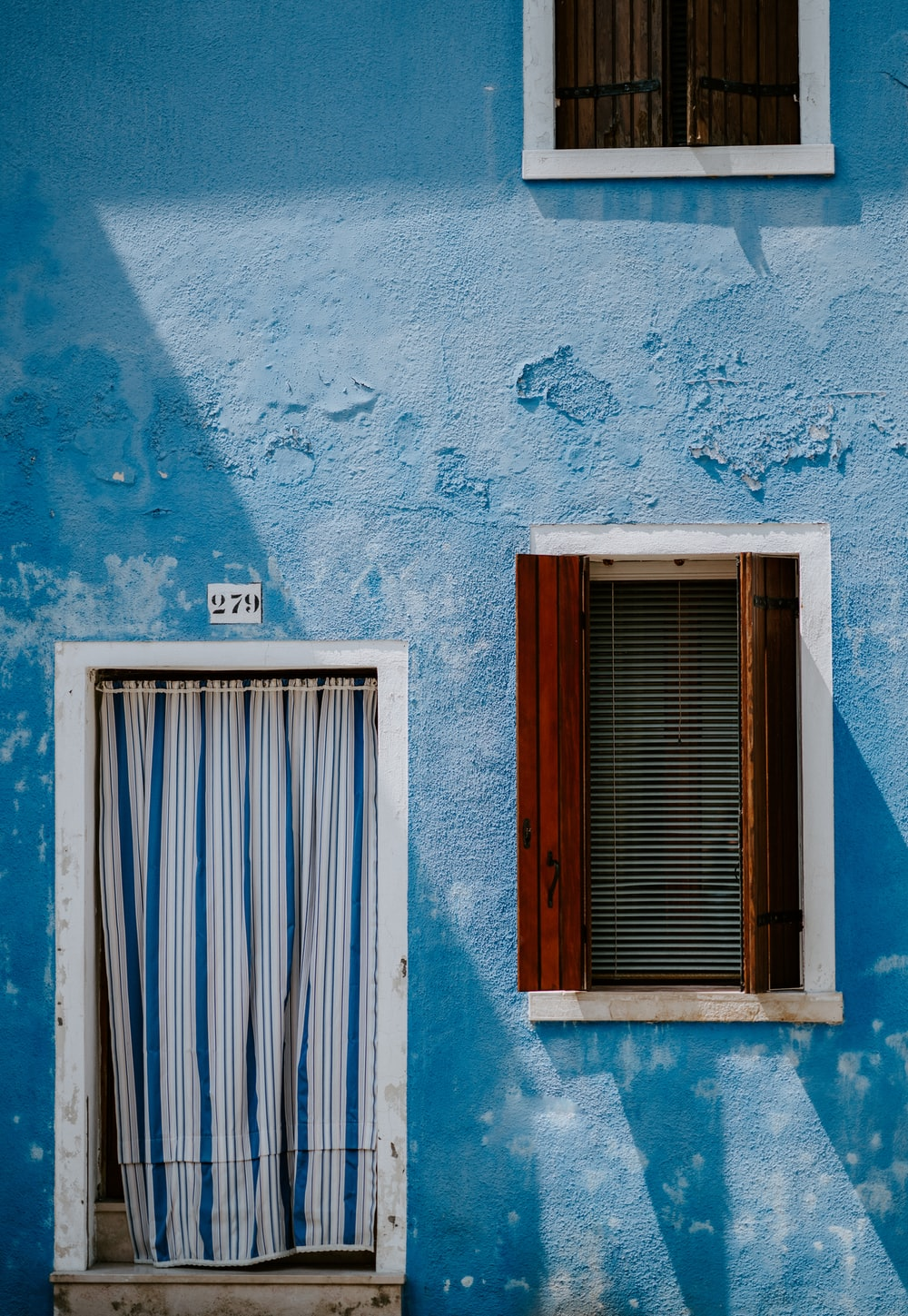 blue house with curtain in door and wooden window