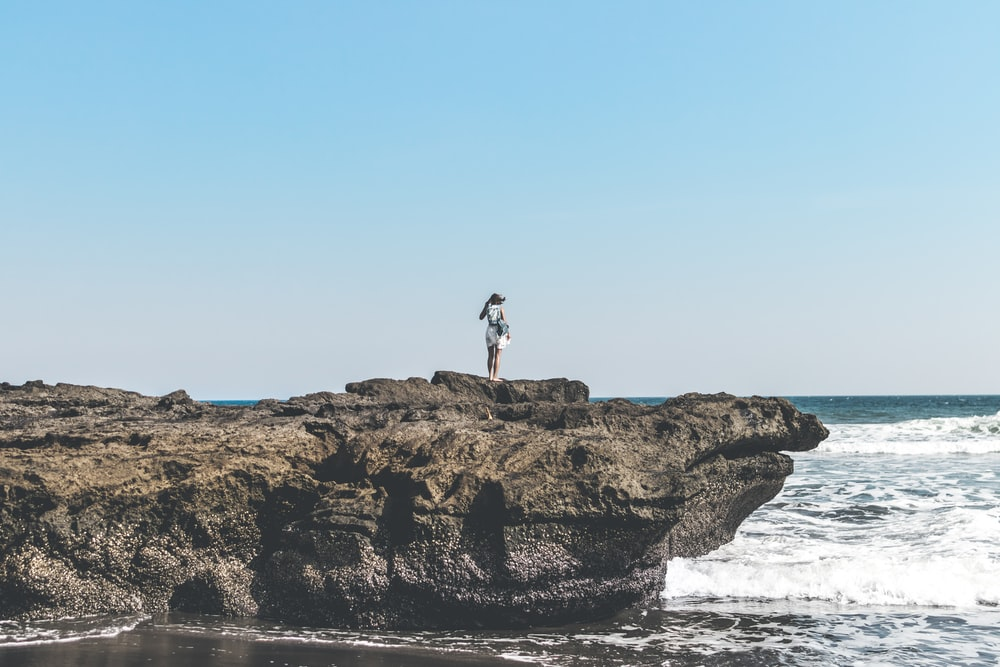 person standing on top of rock formation beside body of water