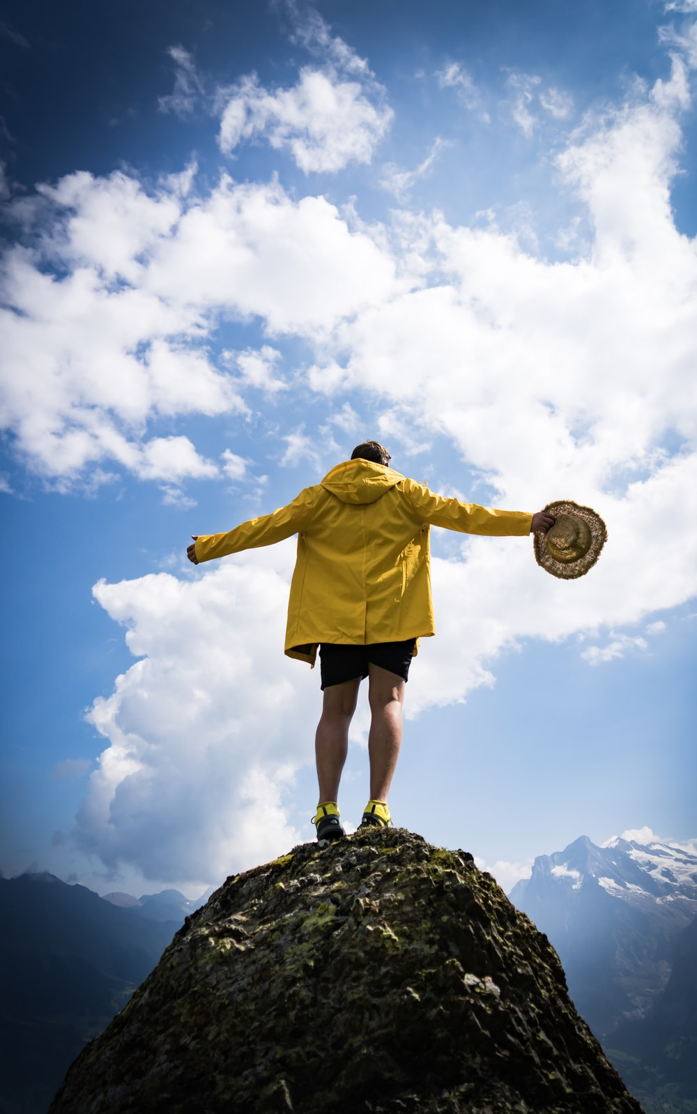 man holding brown strawhat standing on top of rock