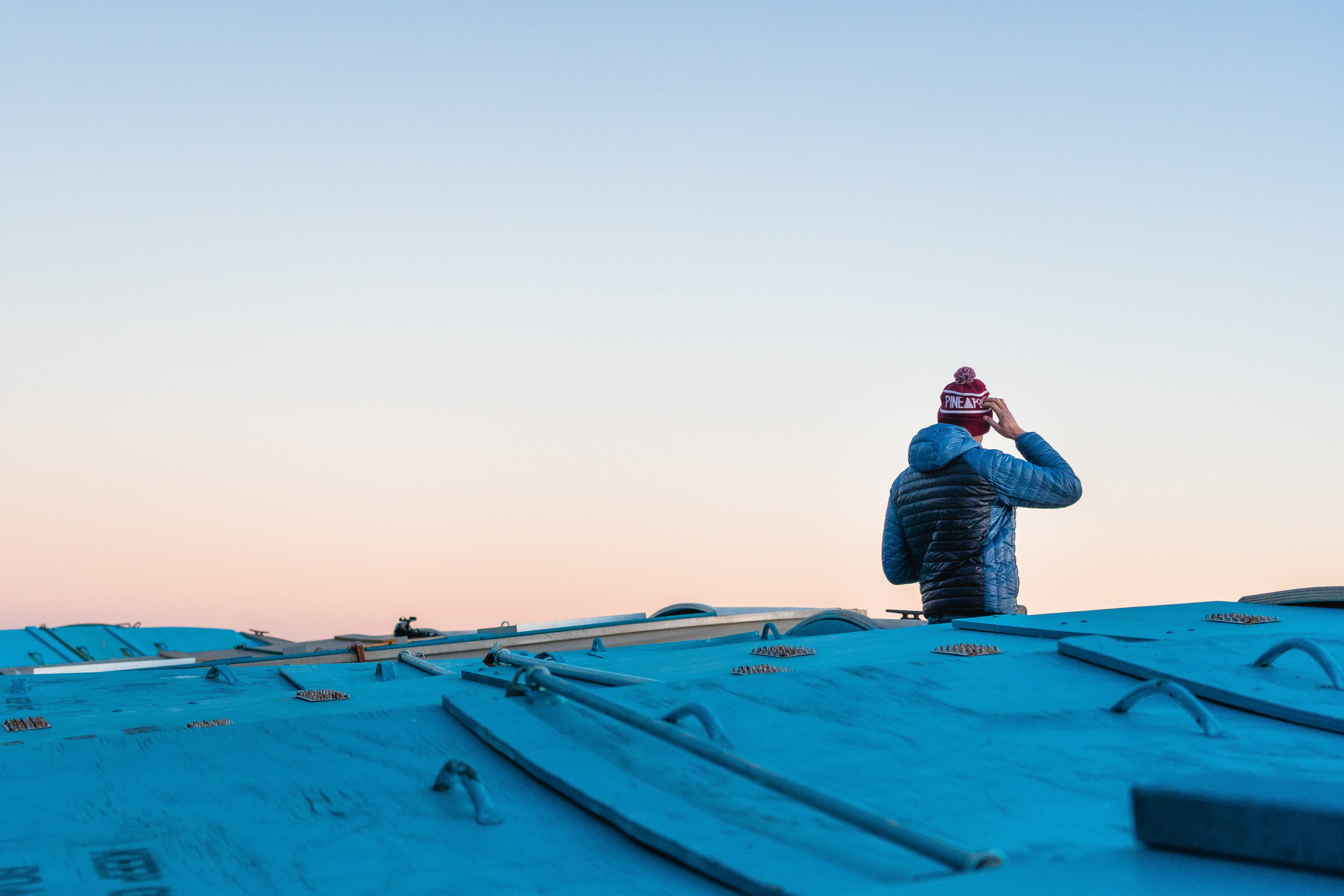 man scratching head on roof top under white sky