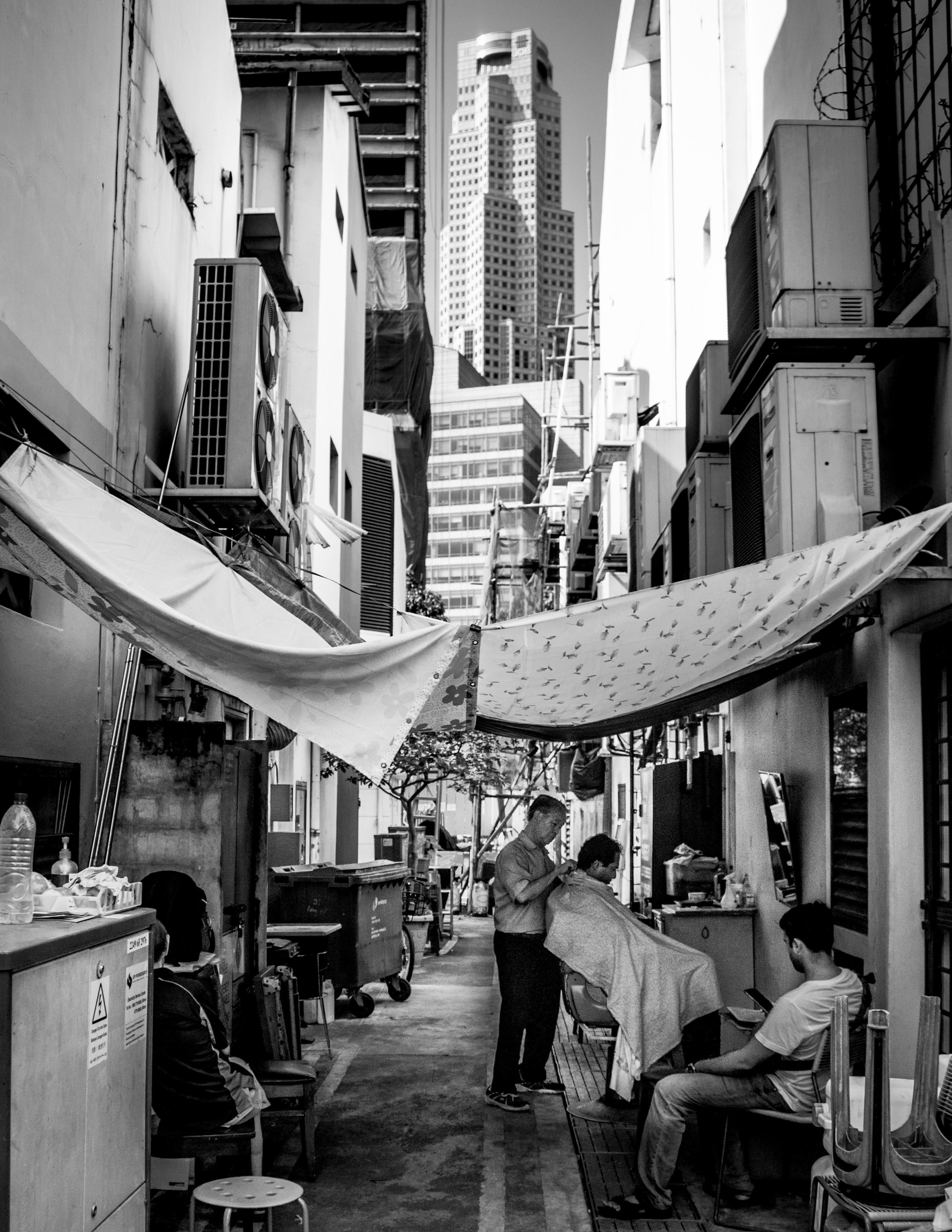 grayscale photo of barbershop outside near buildings