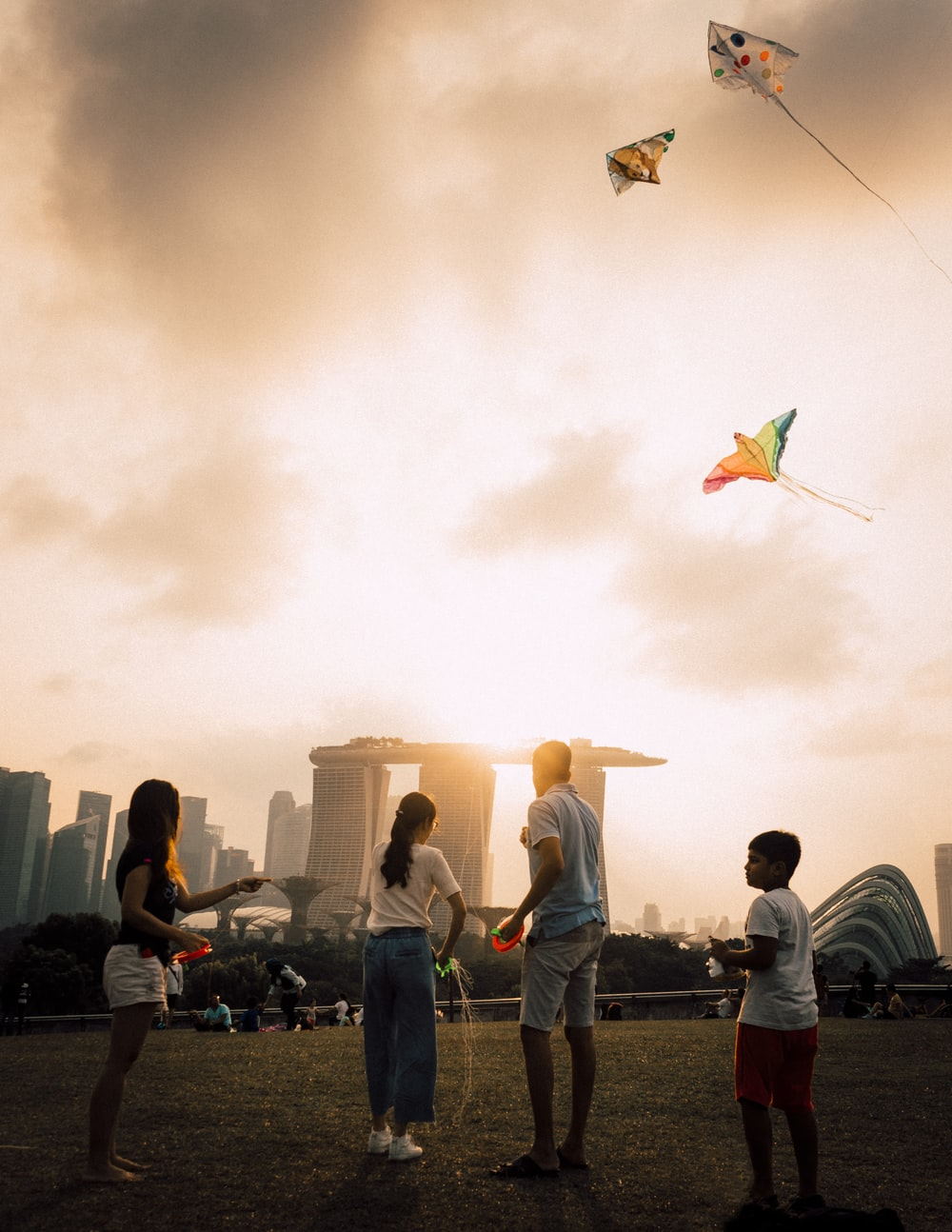 four person playing kite on grass field
