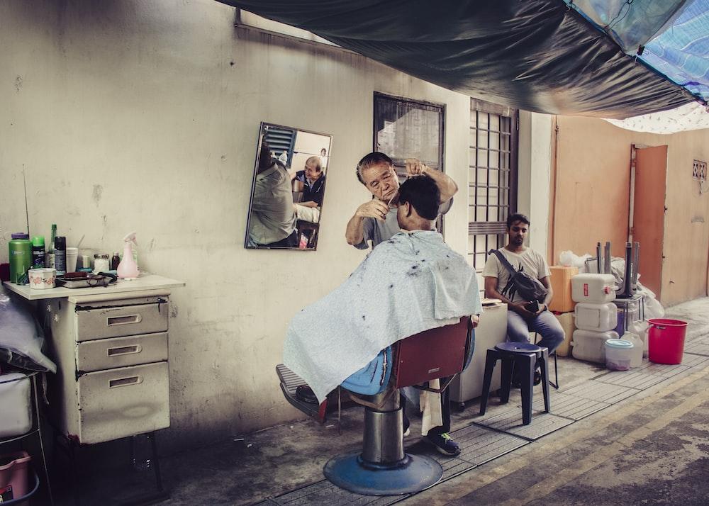 man cutting man's hair