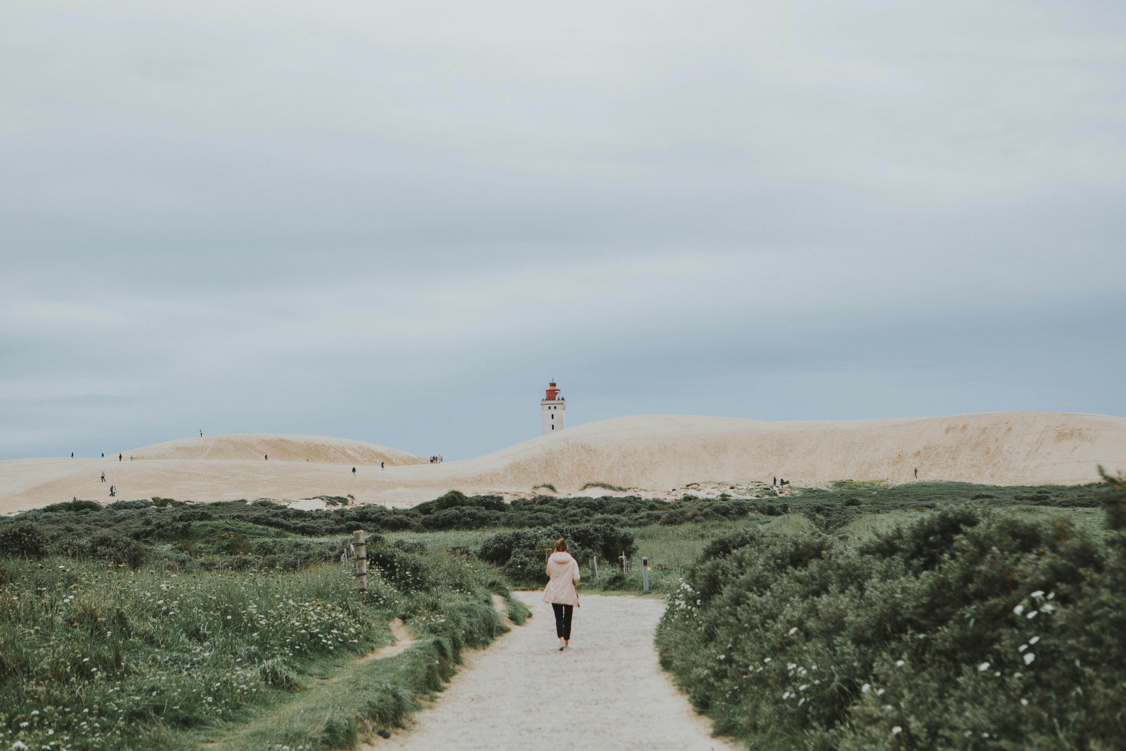 woman walking beside green grasses during daytime