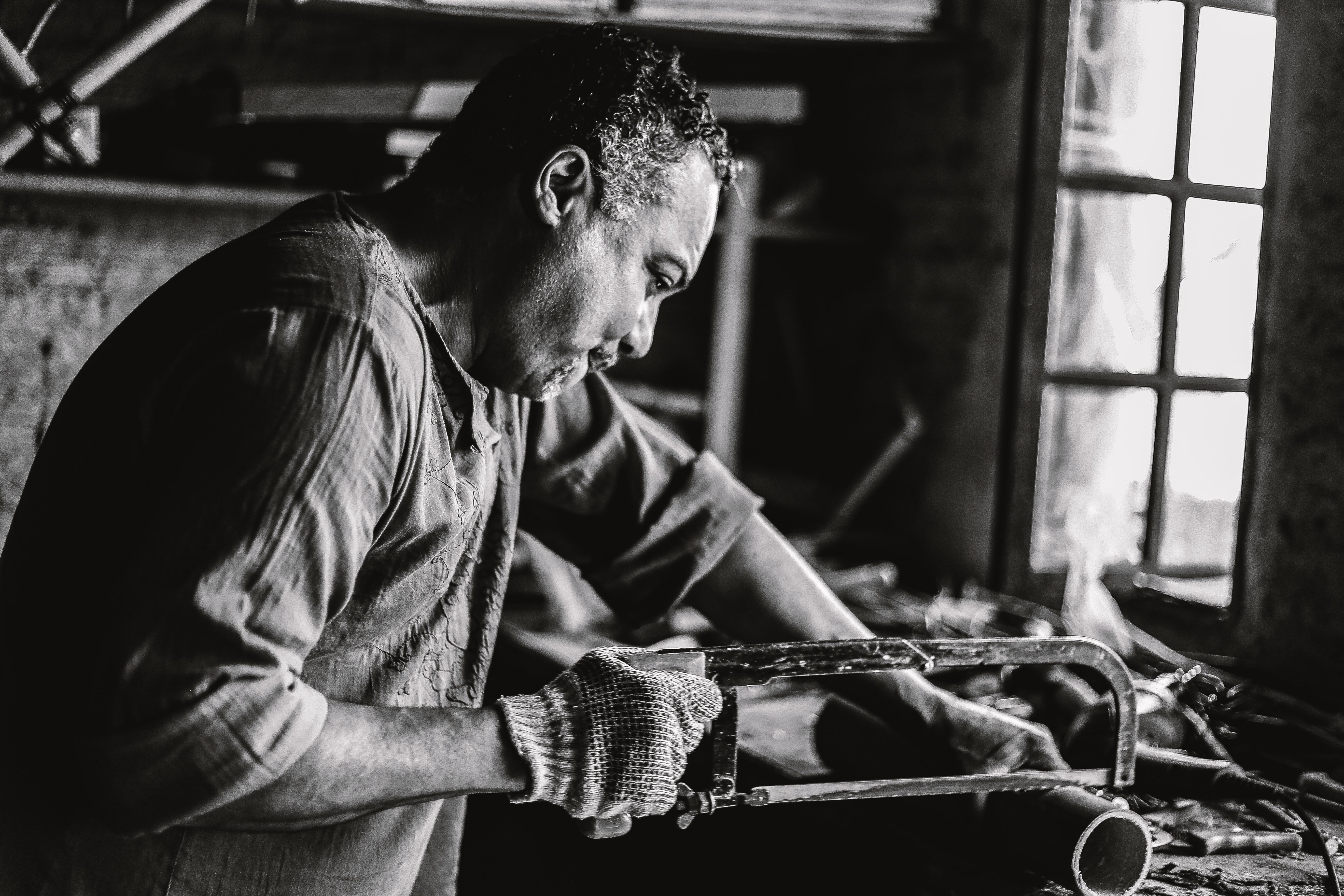man holding hack saw