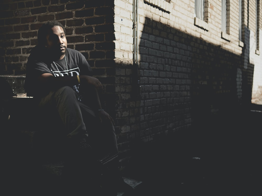 man sitting on gray staircase