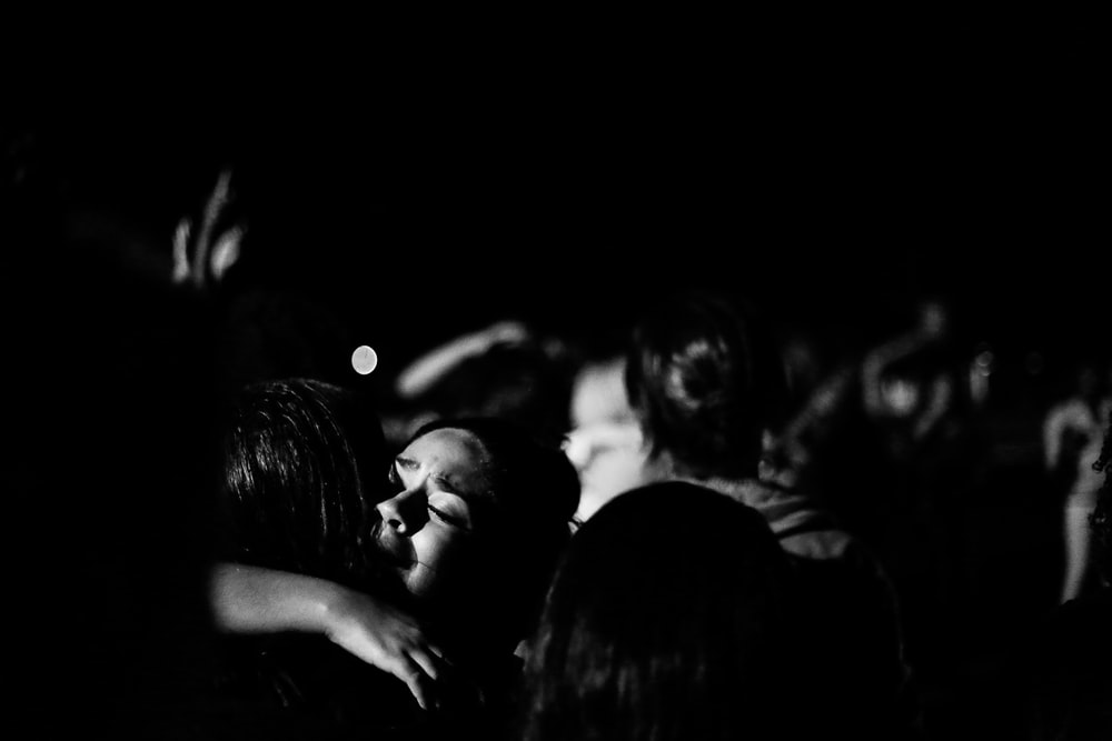grayscale photograph of two person hugging