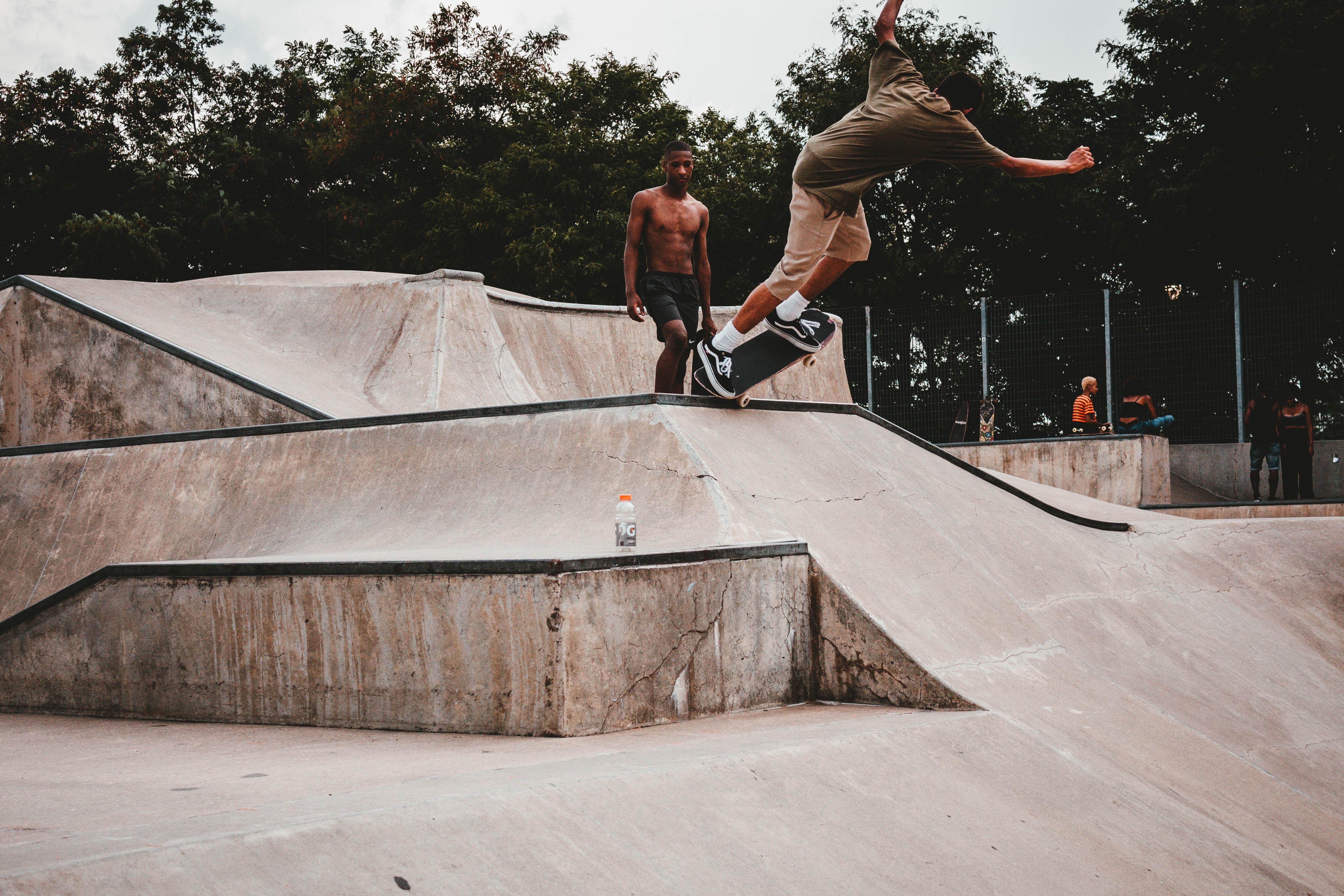 man grinding skateboard on ramp ledge near man