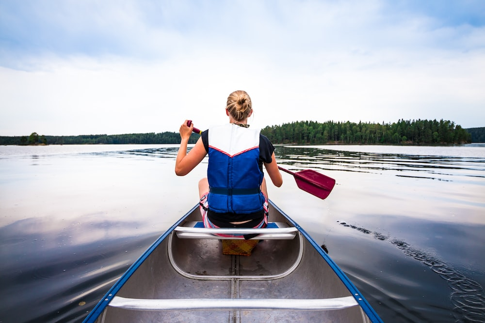 woman holding paddle riding boat on body of water