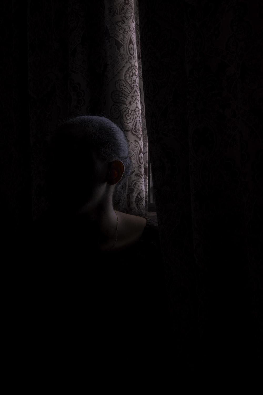 woman beside brown window curtain