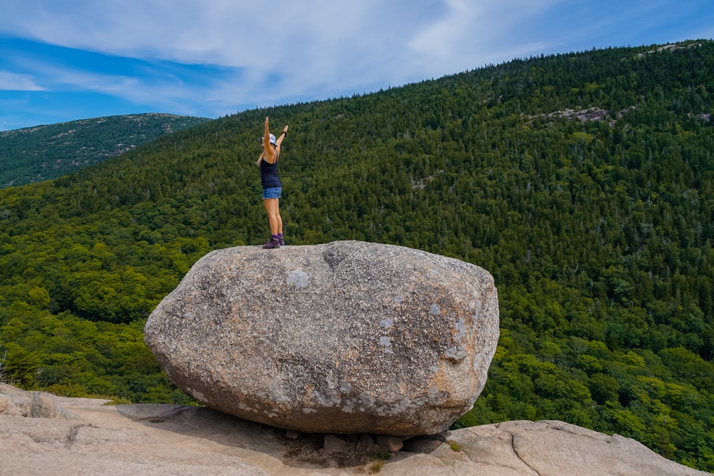 woman standing on rock on mountain