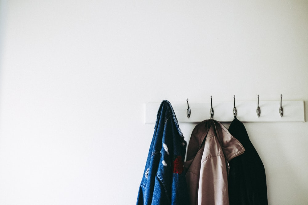 three jacket hanging on wall hooks