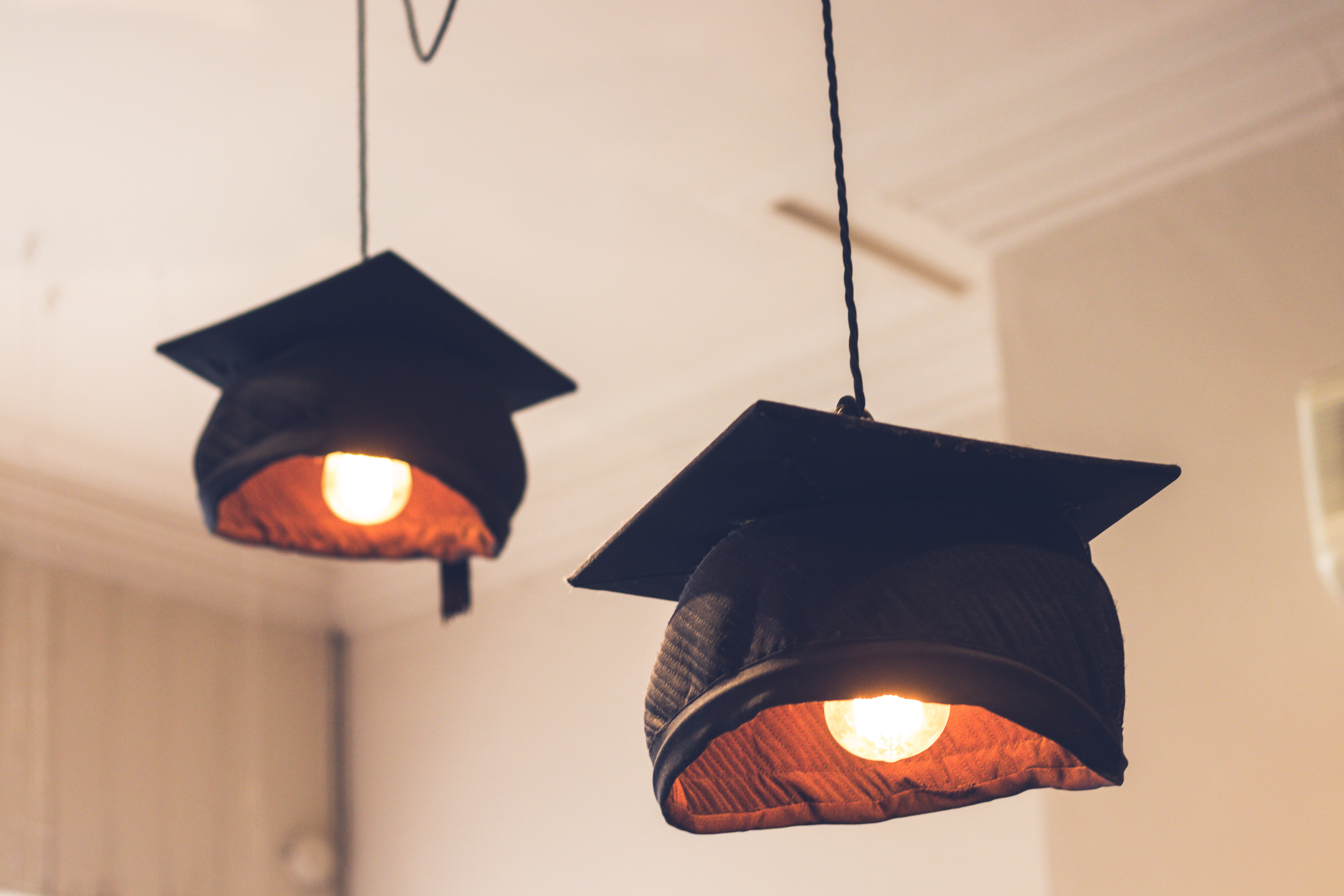 Two graduation caps (black) attached to lightbulbs, acting as lamp covers