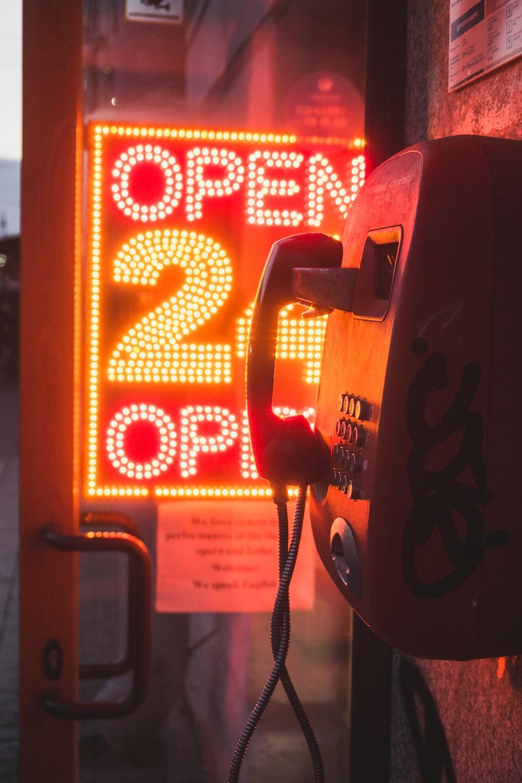 photograph of cradle telephone beside LED signage