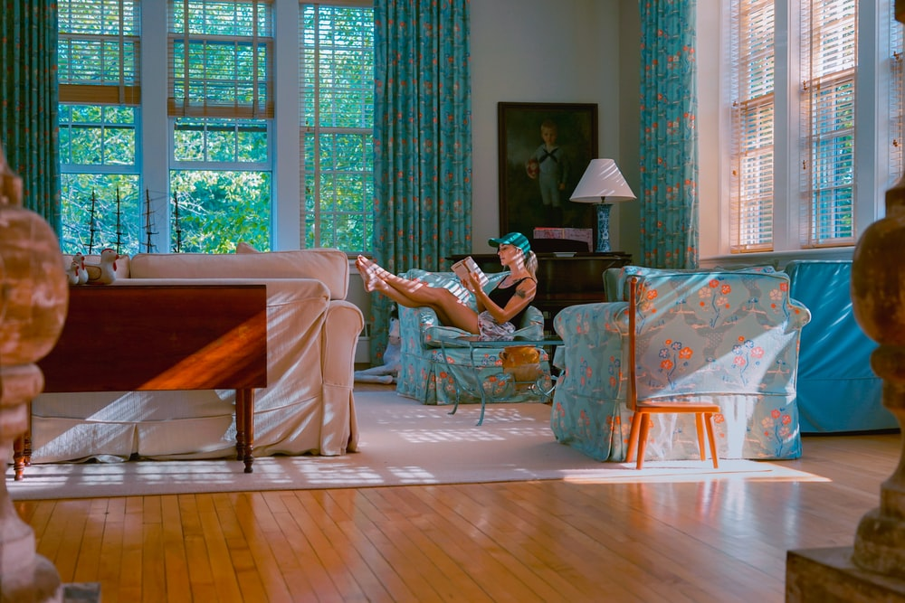 woman sitting on teal and pink floral sofa chair reading a book in room