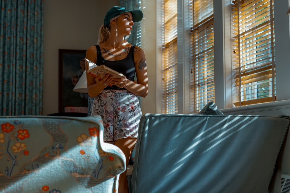 woman holding book while standing beside window blinds