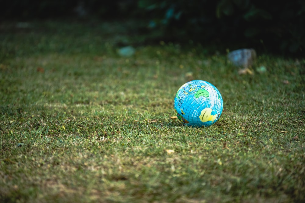 blue and white desk globe on green grass field during daytime