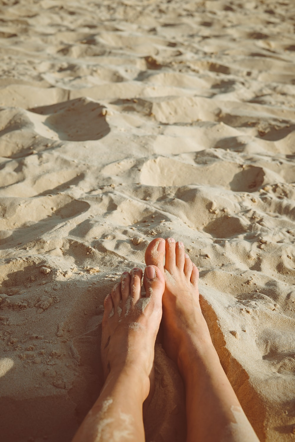 person's feet lying on sand