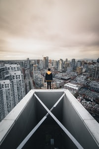 man standing on top of high-rise building