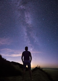 person standing in front of Milky Way startrail