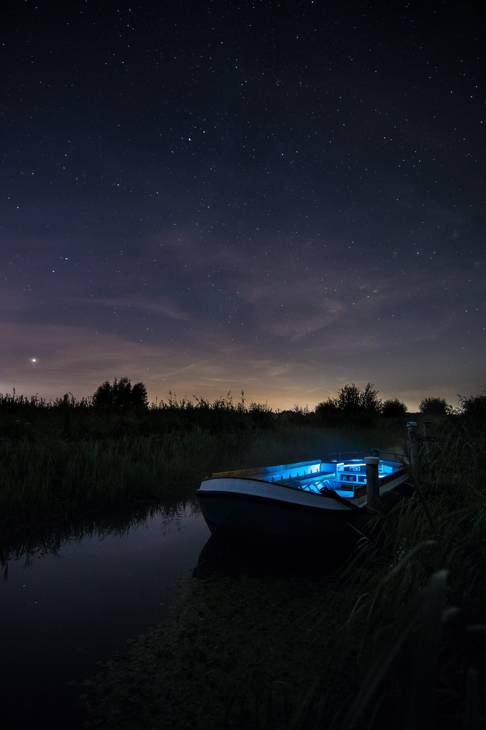 blue and white boat on river between trees at night