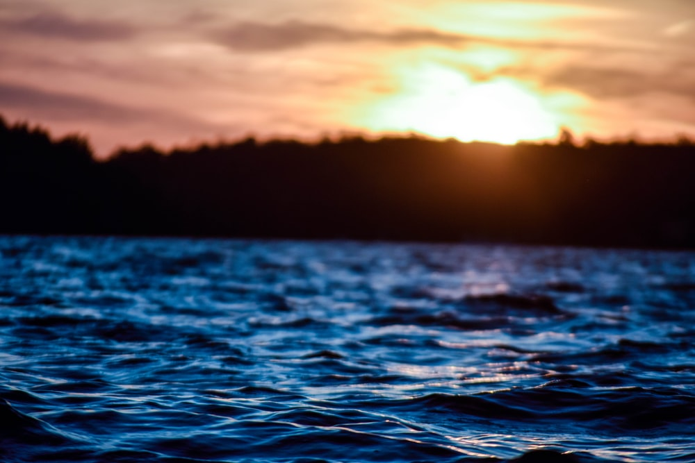 time lapse photography of body of water under golden hour