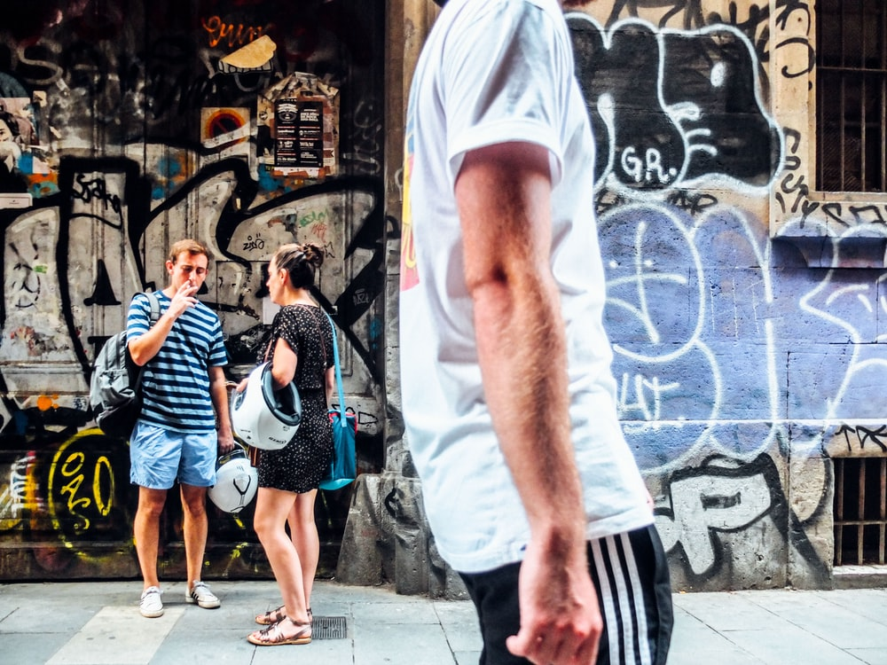 man walking on road with man and woman talking near wall in background
