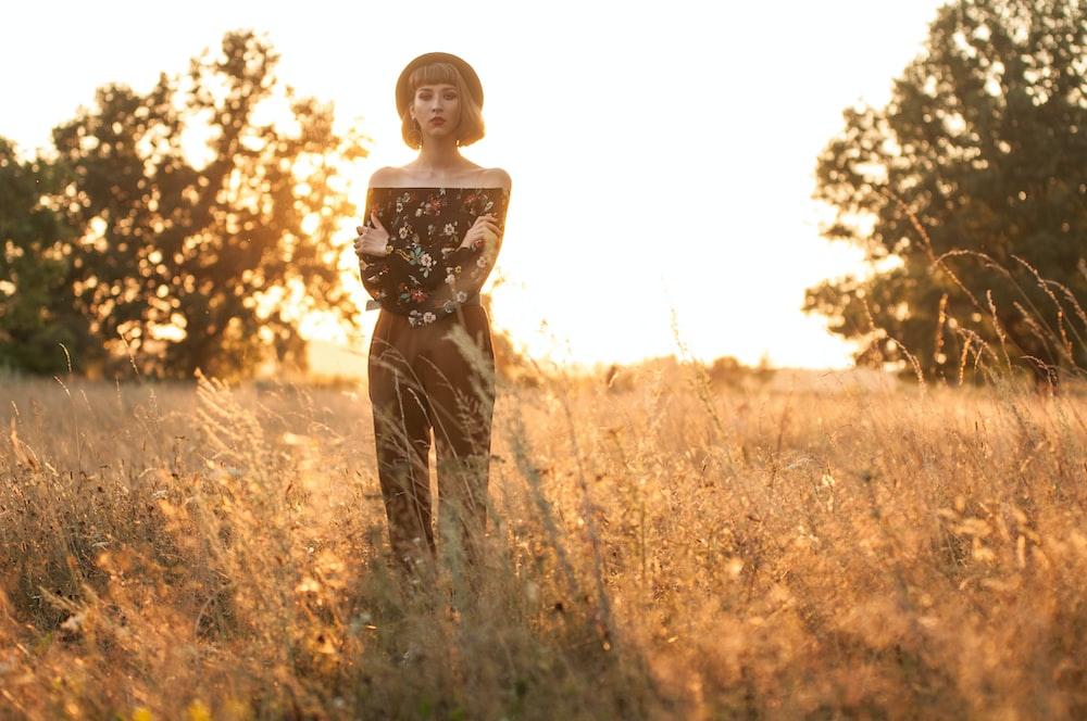 woman standing on grass field near trees