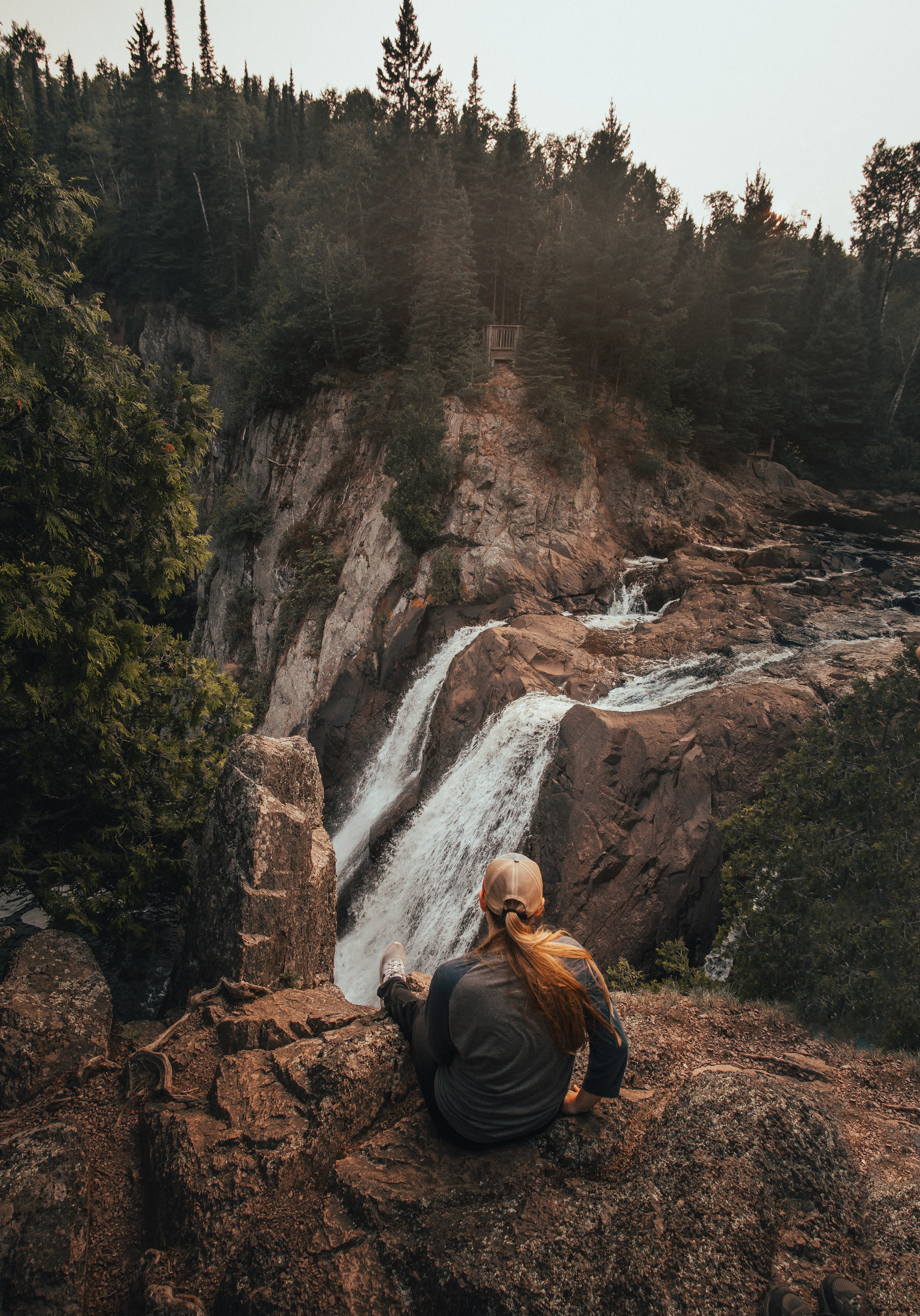 woman sitting in front of waterfalls