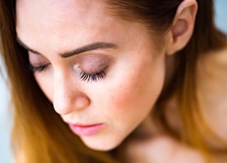 selective focus photography of woman closing her eyes with brown eyeshadow