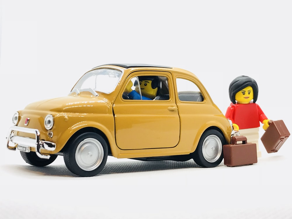 yellow Volkswagen Beetle scale model and two minifigs