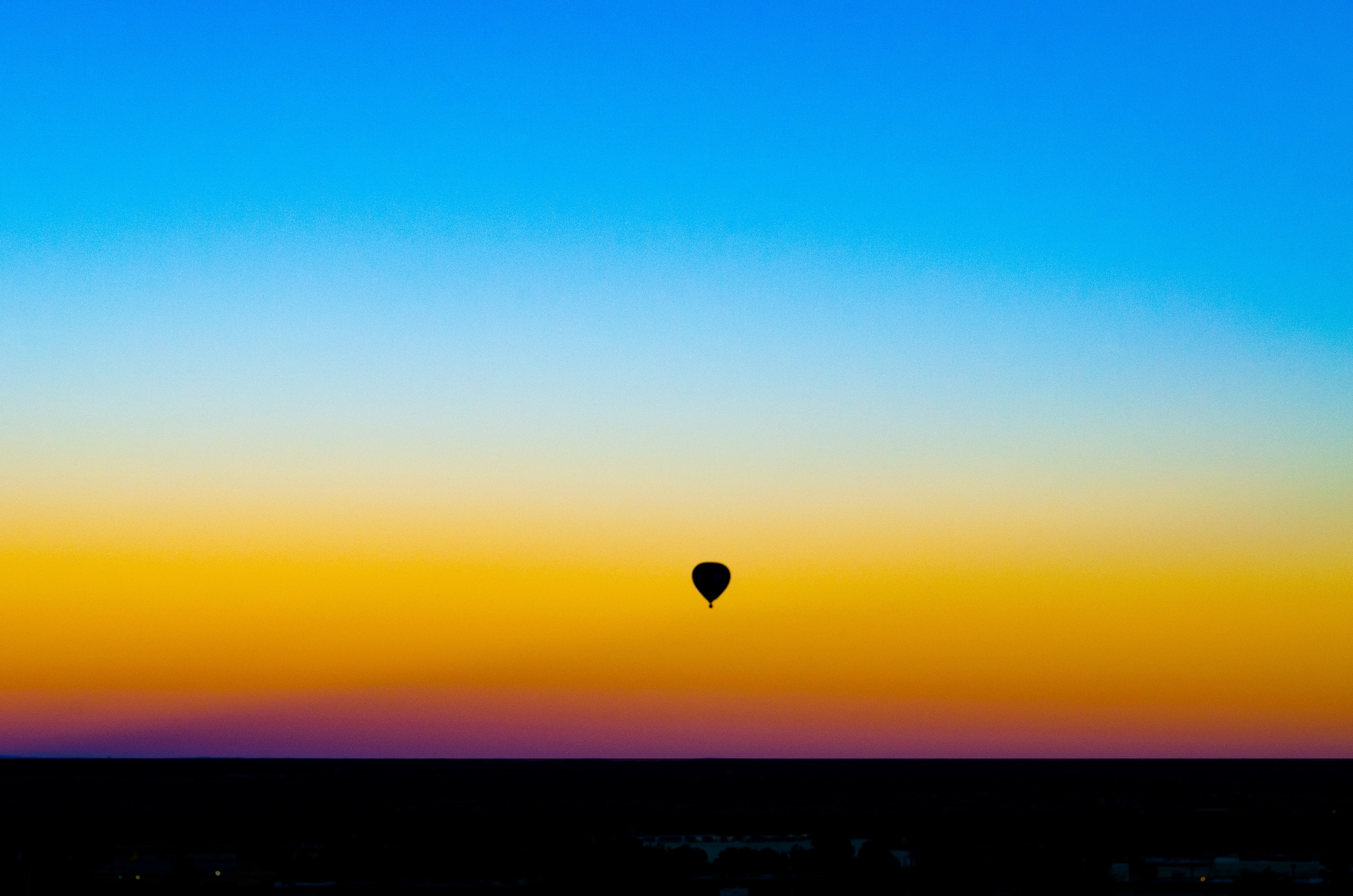 silhouette of hot air balloon under blue sky