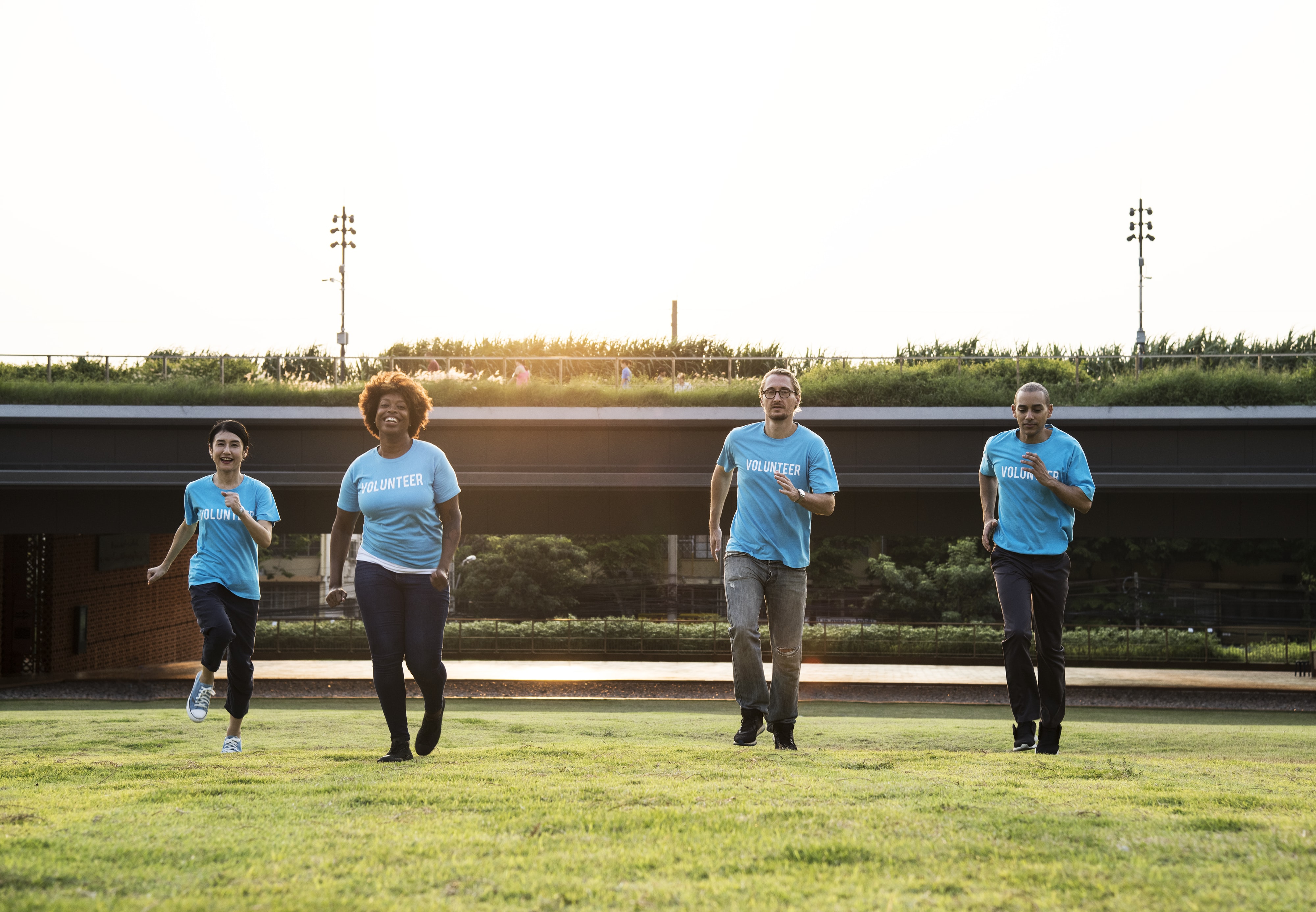 four people wearing blue shirts running on grass field
