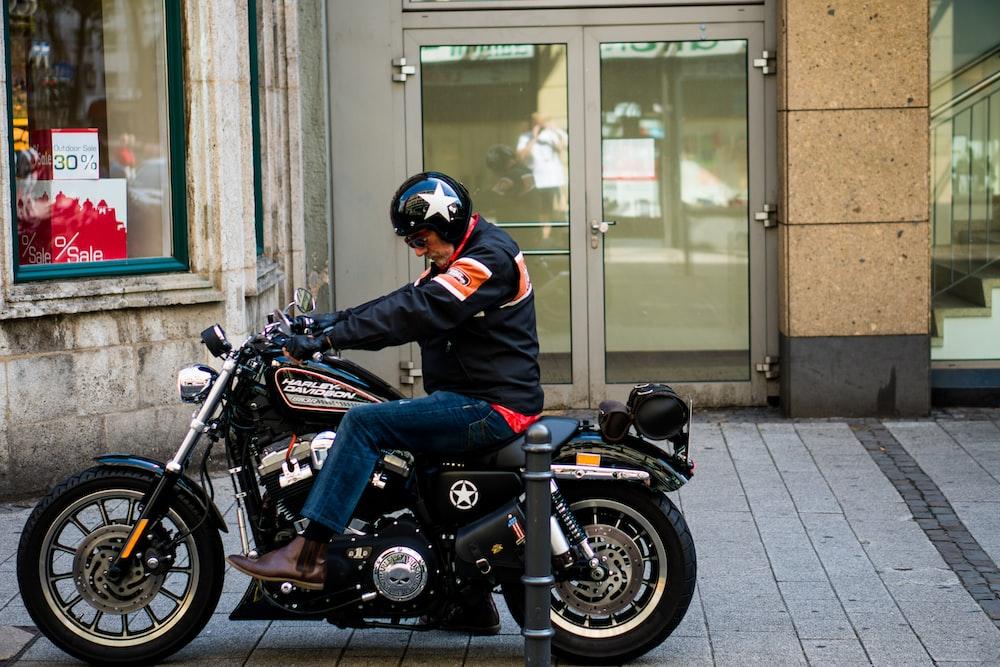 man riding black cruiser motorcycle