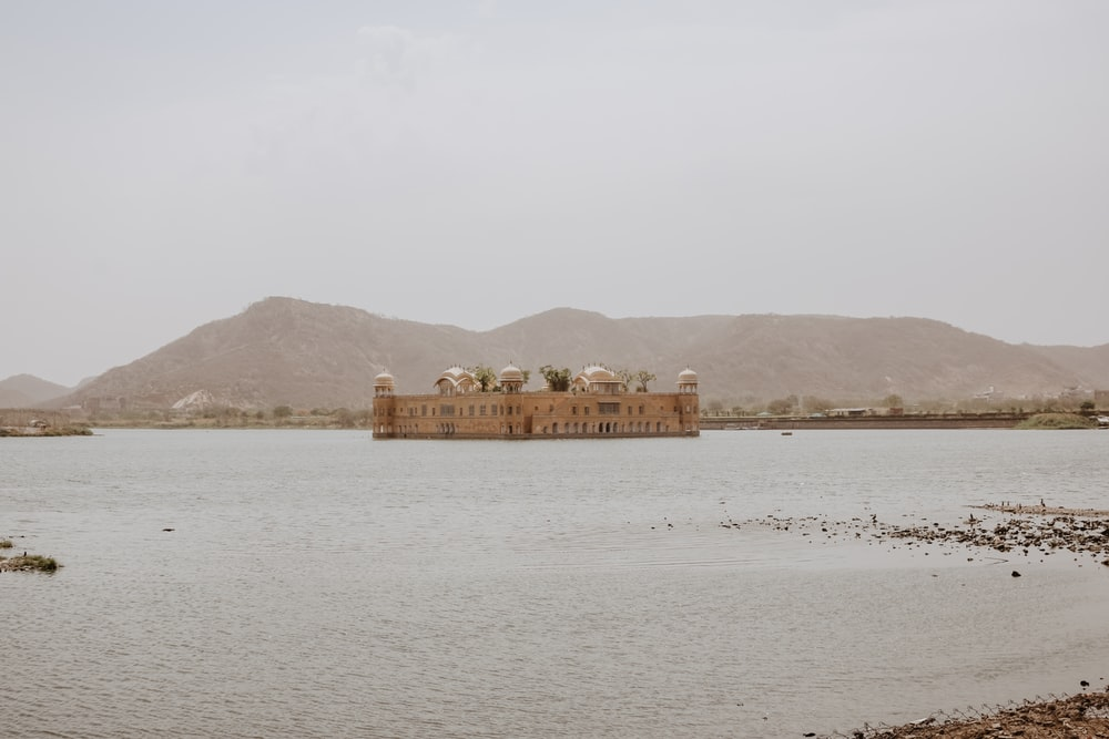 beige concrete temple surrounded by body of water
