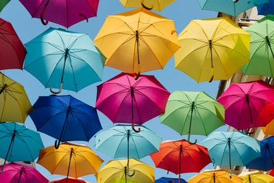 assorted-color umbrella hanging in the air colorful teams background