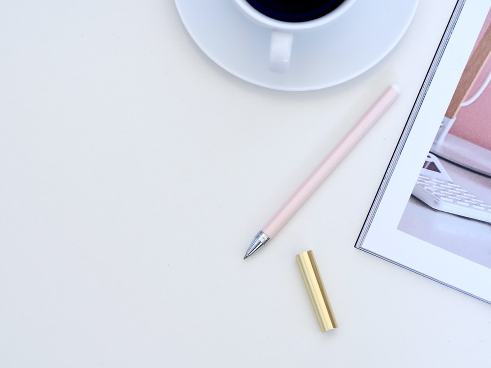 pink pen beside white ceramic teacup on white surface