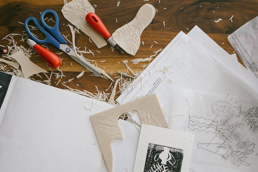 blue scissor near papers