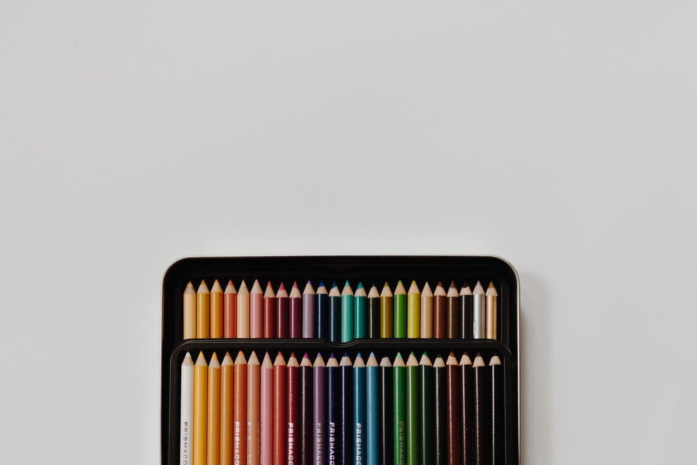 assorted-color pencil set with case on white surface