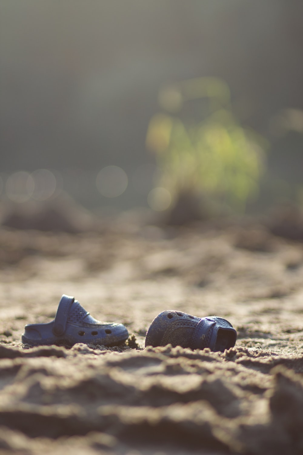 focus photo of pair of boy's black rubber clogs on brown soil at daytime