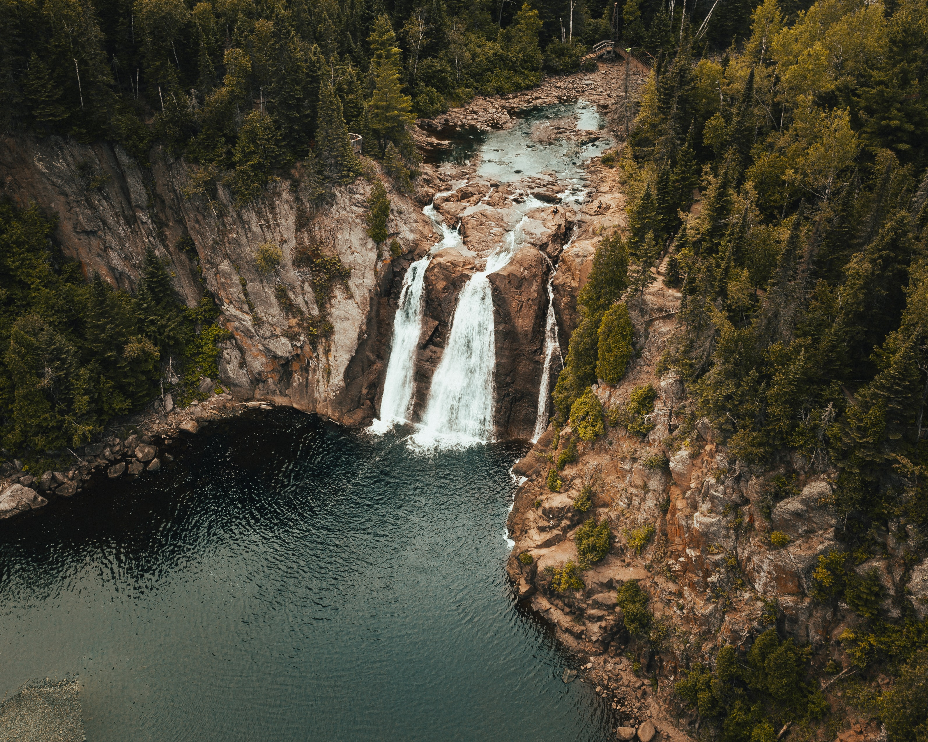 aerial view photography of waterfalls surrounded by pine trees
