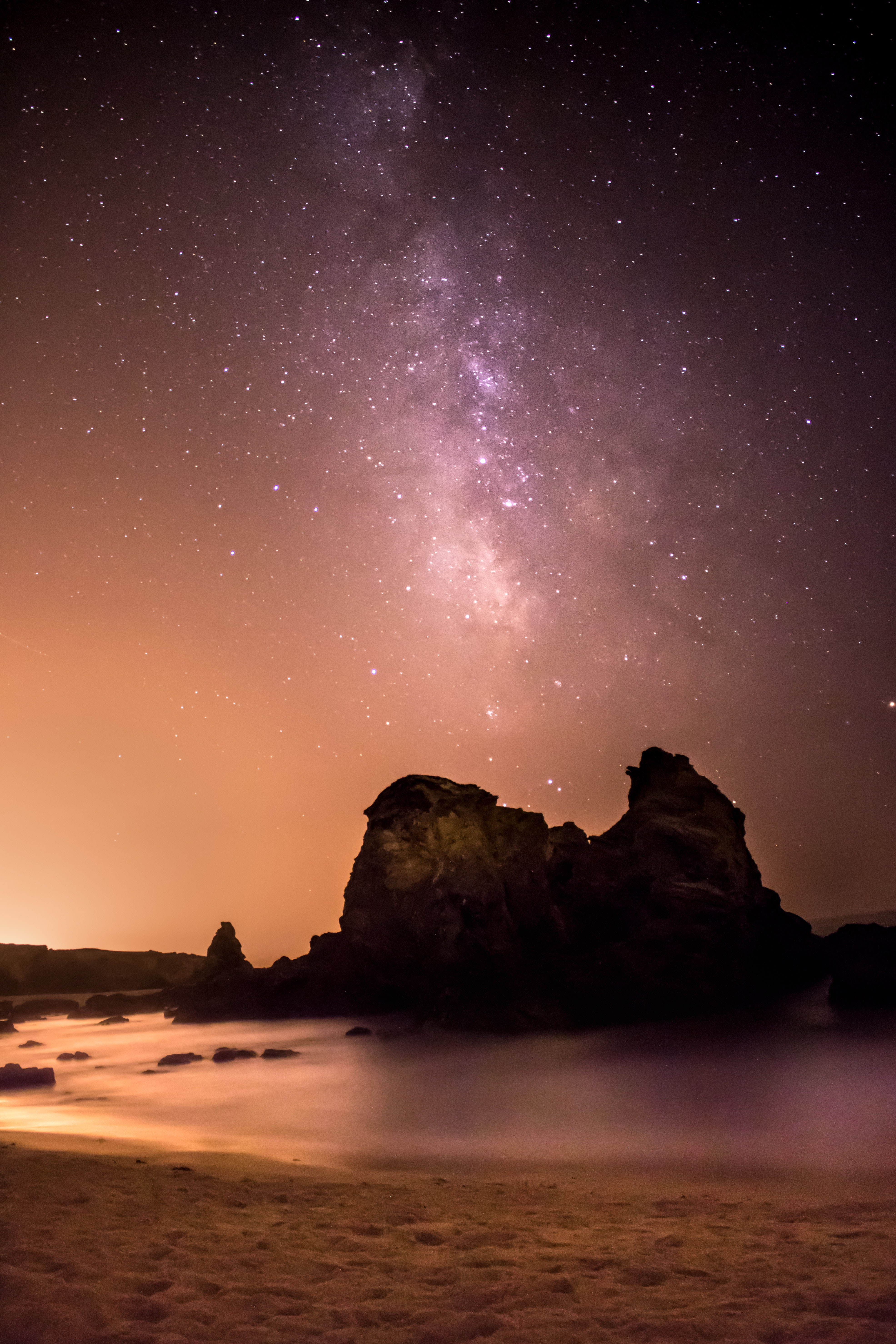 rock formation surrounded by water under black and white milky way
