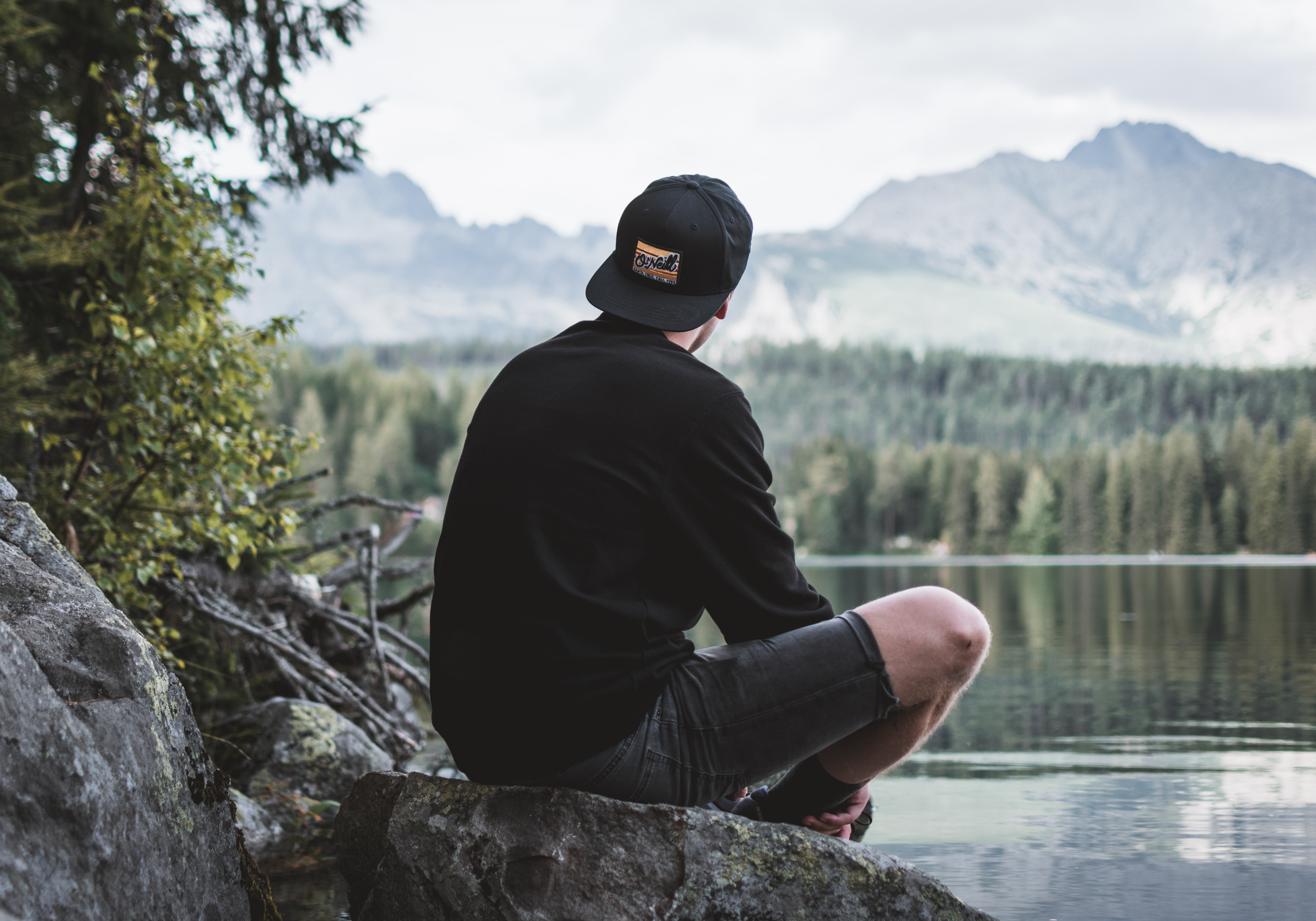 selective focus photography of man sitting on rock while looking at mountains