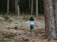 Child running in a forest