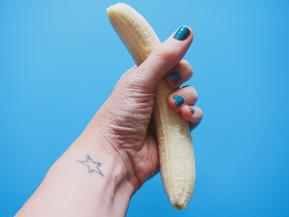 person holding peeled banana fruit