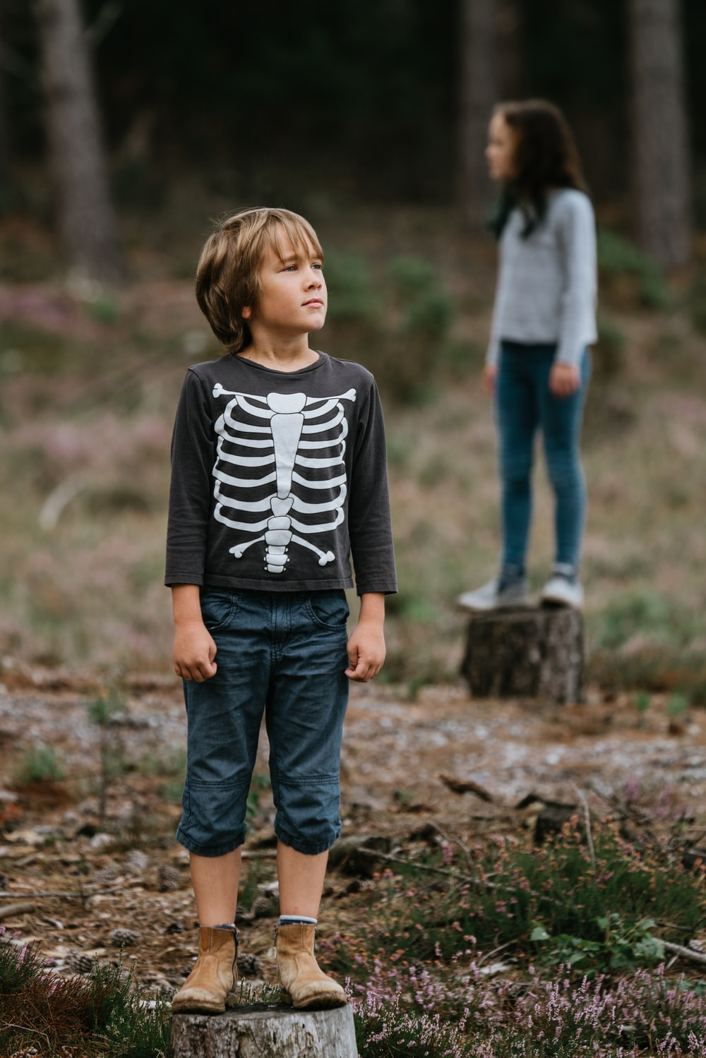 boy wearing black and white skeleton-printed crew-neck sweatshirt while standing on log