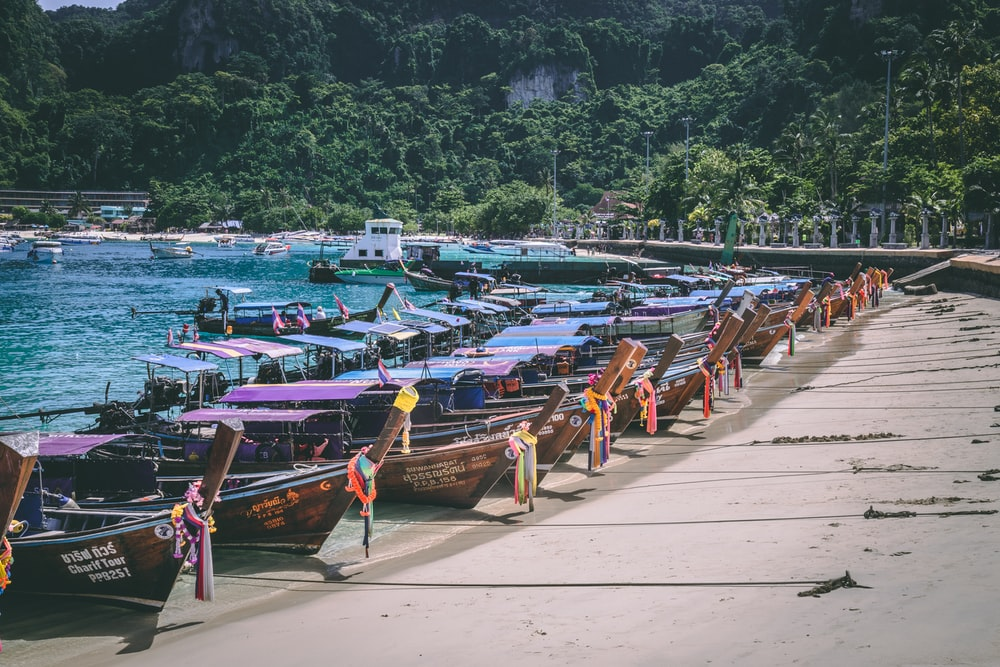 brown wooden boats on sea shore during daytime