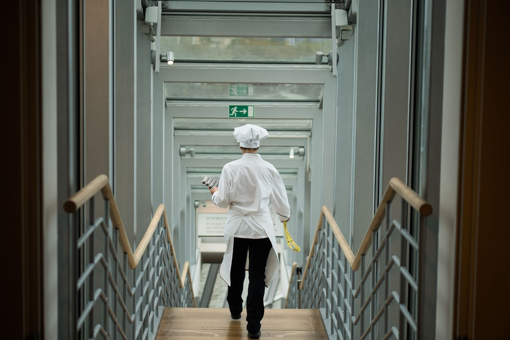 person wearing white apron walkin on stairs